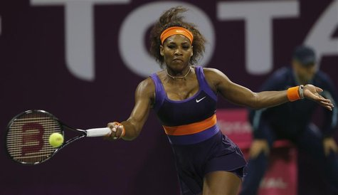 Serena Williams of the U.S. returns the ball to Maria Sharapova of Russia during their women's semi-final match at the Qatar Open tennis tou