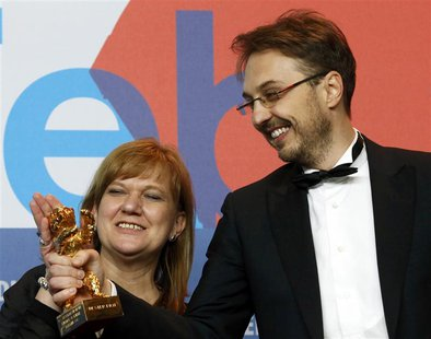 "Director Calin Peter Netzer and producer Ada Solomon look at the Golden Bear award received for the Best Film for ""Pozitia Copilului"" (Child"