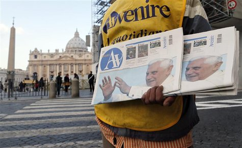 A newspaper seller shows newspapers with photographs of Pope Benedict XVI outside the Vatican February 17, 2013. Thousands of people are exp
