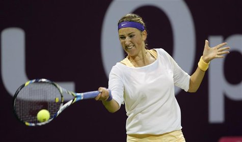 Victoria Azarenka of Belarus returns the ball to Agnieszka Radwanska of Poland during their women's semi-final match at the Qatar Open tenni