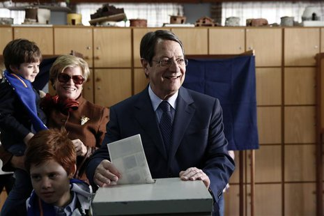 Cyprus presidential candidate Nicos Anastasiades (C) of the right wing Democratic Rally party casts his ballot as his wife Andriana and his