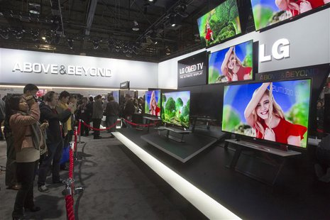 Showgoers look at a display of 55-inch OLED televisions in the LG Electronics booth during the first day of the Consumer Electronics Show (C