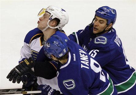 St. Louis Blues Vladimir Tarasenko (L) is checked by Vancouver Canucks Chris Tanev and Aaron Volpatti (R) during the second period of their