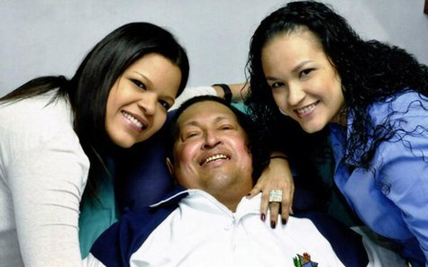 Venezuela's President Hugo Chavez smiles in between his daughters, Rosa Virginia (R) and Maria while recovering from cancer surgery in Havan