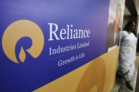 A woman walks past a poster of Reliance Industries installed outside the venue of the company's annual general meeting in Mumbai June 7, 201