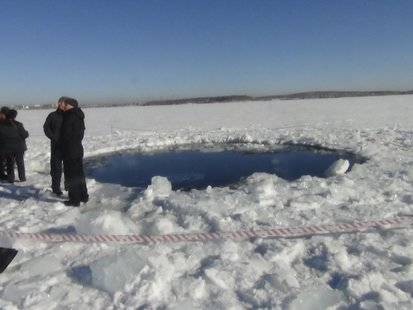 Russian police work near an ice hole, said by the Interior Ministry department for Chelyabinsk region to be the point of impact of a meteori