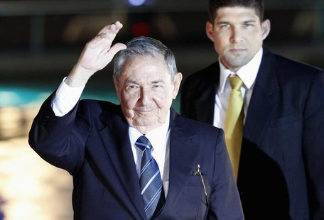 Cuba's President Raul Castro waves to the media before an official dinner at La Moneda Presidential Palace during the summit of the Communit
