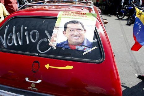 "A car with a picture and poster of Venezuela's President Hugo Chavez and the word ""he's back' drives past a military hospital, where Chavez"