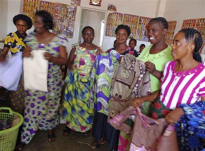 Members of a sewing circle run by woman entrepreneurs pose with garments in the town of Fungurume, close to Tenke Fungurume, a copper and co