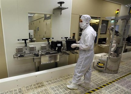 An employee carries a wafer box in a clean room of German semiconductor manufacturer Infineon in Regensburg February 12, 2013. REUTERS/Micha