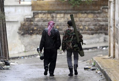 Members of the Free Syrian Army walk with their weapons in Al Izaa district in Aleppo February 16, 2013. REUTERS/Muzaffar Salman