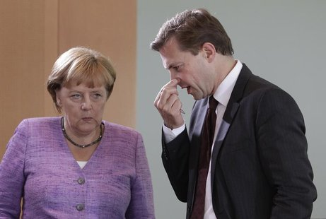 German Chancellor Angela Merkel chats with German government spokesman Steffen Seibert (R) before the weekly cabinet meeting in Berlin, Sept