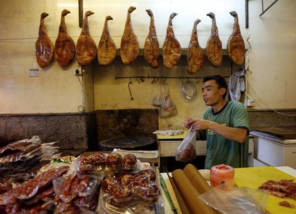 A man works in his shop selling pork products in Shanghai September 28, 2007. REUTERS/David Gray