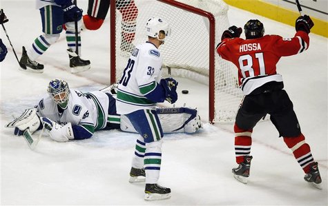 Chicago Blackhawks' Marian Hossa (R) celebrates his goal on Vancouver Canucks' Cory Schneider (L) as Canucks' Henrik Sedin looks on during t
