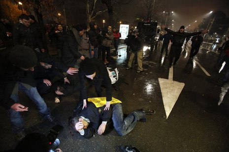 Protesters lie on the ground after clashes with riot police during a protest against high electricity prices in Sofia February 19, 2013. REU
