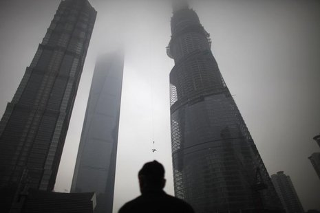 A man watches a construction crane lift a piece of steel at the Shanghai Tower (R) at the financial district of Pudong in Shanghai January 2