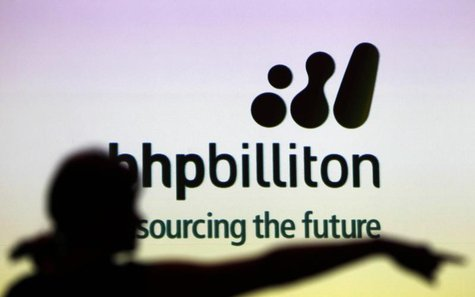 A woman gestures in front of a BHP Billiton sign during a half-year results briefing in Sydney in this February 16, 2011 file photo. REUTERS