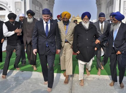 Britain's Prime Minister David Cameron (4th R) walks inside the premises of the holy Sikh shrine of Golden temple in the northern Indian cit
