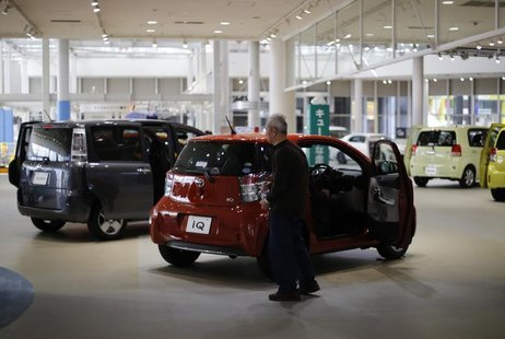 A visitor looks at Toyota Motor Corp cars at the company's showroom in Tokyo February 5, 2013. REUTERS/Toru Hanai