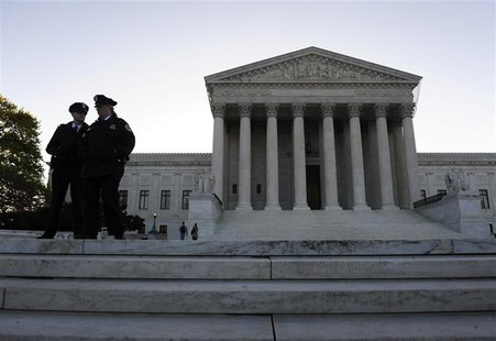 Police officers stand on the front steps on the first day of legal arguments over the Patient Protection and Affordable Care Act at the Supr