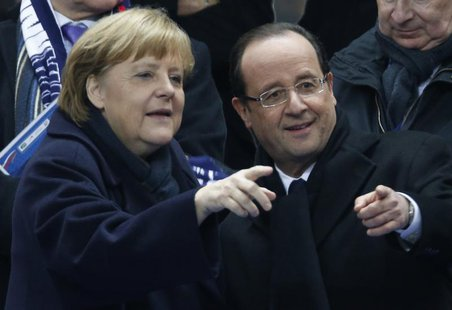 France's President Francois Hollande (R) points with German Chancellor Angela Merkel as they attend an international friendly soccer match b
