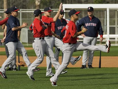 Boston Red Sox manager John Farrell (R) watches his players warm up during a workout at the team's MLB spring training complex in Fort Myers