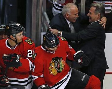 Chicago Blackhawks' head coach Joel Quenneville (back 2nd R) is congratulated after his team's win over the Vancouver Canucks in their NHL hockey game in Chicago, Illinois, February 19, 2013.  REUTERS/Jim Young
