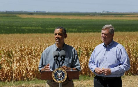 U.S. President Barack Obama talks next to U.S. Secretary of Agriculture Tom Vilsack after they tour the McIntosh family farm with the owners