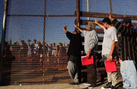 A group of recently deported immigrants stand near the double steel fence that separates San Diego and Tijuana at the border in Tijuana Dece
