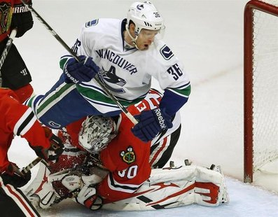 Vancouver Canucks' Jannik Hansen (top) crashes into Chicago Blackhawks' goalie Ray Emery during the third period of their NHL hockey game in