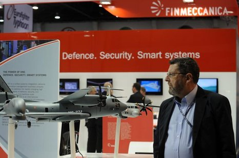A visitor walks past a stand for Italian defence group Finmeccanica during the International Defence Exhibition and Conference (IDEX) at the