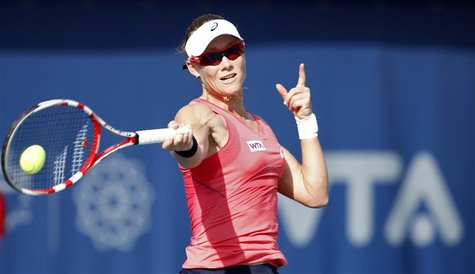 Samantha Stosur of Australia hits a return to Roberta Vinci of Italy during their women's singles quarter-final match at the WTA Dubai Tenni