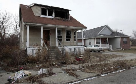 A vacant and blighted house sits next to a well-kept occupied house in a once thriving eastside neighborhood in Detroit, Michigan January 23