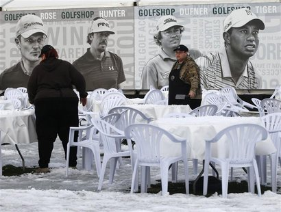 Concession workers clear snow from tables as weather on the golf course continues to delay first round play of the WGC-Accenture Match Play