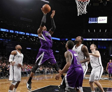 Sacramento Kings forward Thomas Robinson (2nd L) shoots over Kings guard Aaron Brooks (C), and Brooklyn Nets guard C.J. Watson (L), forward