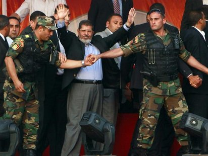 Egypt's Islamist President-elect Mohamed Mursi waves to his supporters while surrounded by his members of the presidential guard in Cairo's