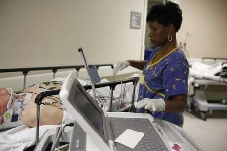 EKG technician Diana Goodie (R) performs an electrocardiogram on a patient in the hallway of the emergency room at Ben Taub General Hospital