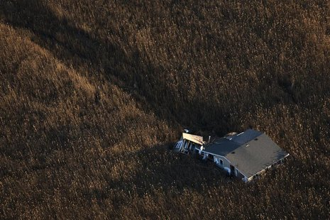 An aerial view shows a house pushed into marshland almost a month after the Oakwood neighborhood in the Staten Island borough of New York wa