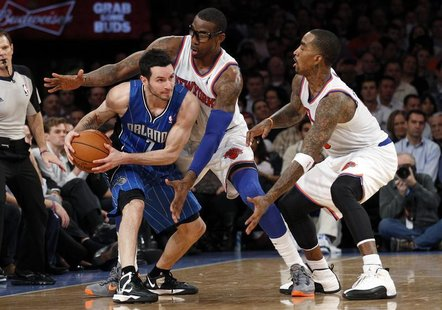 Orlando Magic's guard J.J. Redick (L) looks to pass the ball while being defended by New York Knicks' guard J.R. Smith (R) and Knicks forwar