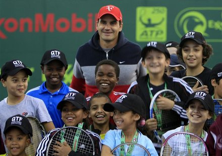 Roger Federer of Switzerland poses with the Qatari Tennis team children during the opening of the Qatar Open tennis tournament in Doha in th
