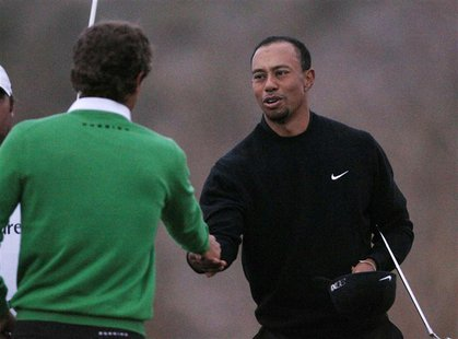 Tiger Woods of the U.S. shakes hands on the 17th green losing 2&1 to Charles Howell III of the U.S. during the weather delayed first round o