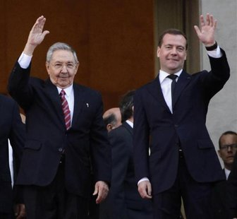 Russia's Prime Minister Dmitry Medvedev and Cuban President Raul Castro (L) wave at the entrance of the Revolution Palace in Havana, Februar