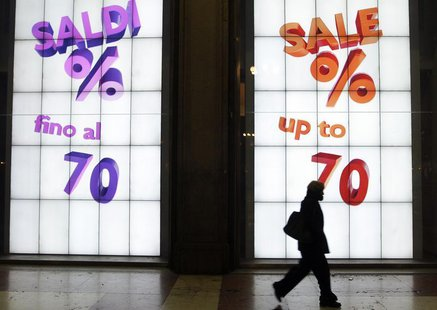 A woman walks past a sale sign in the window of a shop in downtown Milan, January 31, 2012. REUTERS/Stefano Rellandini