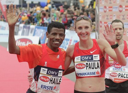 Ethiopian world marathon record holder Haile Gebrselassie and Paula Radcliffe of the UK wave to the crowd after the half marathon race durin