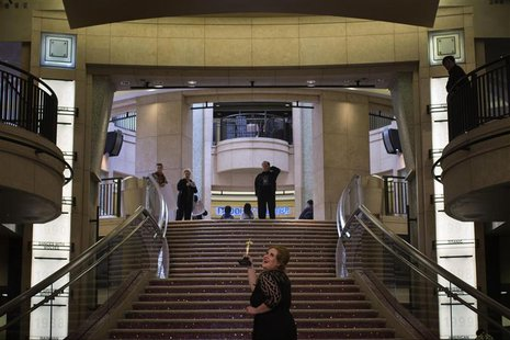 A woman poses for photos along the steps leading to the Dolby Theatre, the site for the 85th Academy Awards in Los Angeles, California Febru