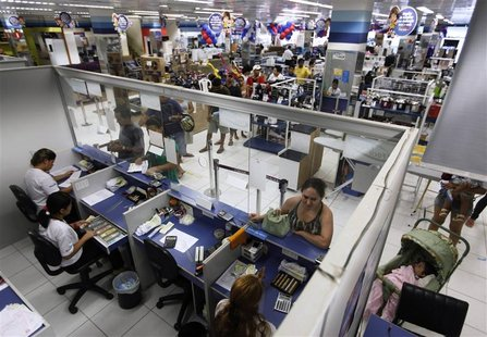 People wait in line at a branch of Bradesco bank, inside a Casas Bahia store in Sao Paulo February 18, 2013. After a spending spree in recen