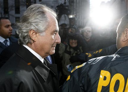 Disgraced financier Bernard Madoff is escorted by police and photographed by the media as he departs U.S. Federal Court after a hearing in N