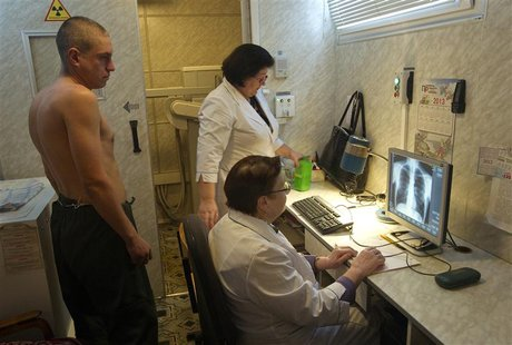 A man (L) is x-rayed to detect tuberculosis during a medical examination, organized by the Belarusian Red Cross society, in Minsk, January 2