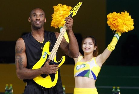 NBA basketball player Kobe Bryant of the U.S. poses with an electric guitar during a charity basketball game in Shanghai August 18, 2012. RE