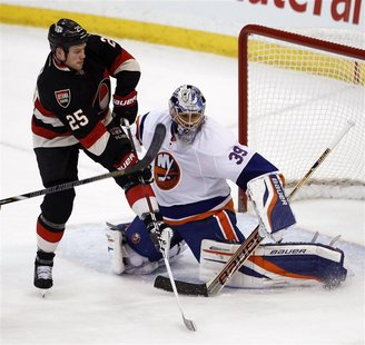 New York Islanders goalie Rick DiPietro (R) makes a save against Ottawa Senators Chris Neil during the second period of their NHL hockey gam